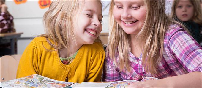 Kaksi lasta nauravat yhdessä oppitunnilla.