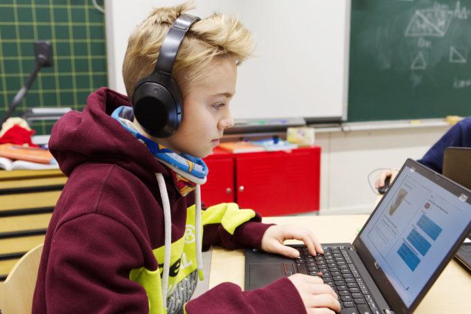 Kuvassa poika kuulokkeet päässä tietokoneen äärellä.