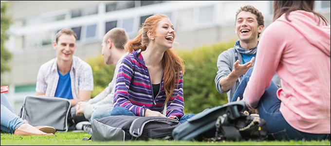 Korkeakouluopiskelijoita istumassa nurmikolla.