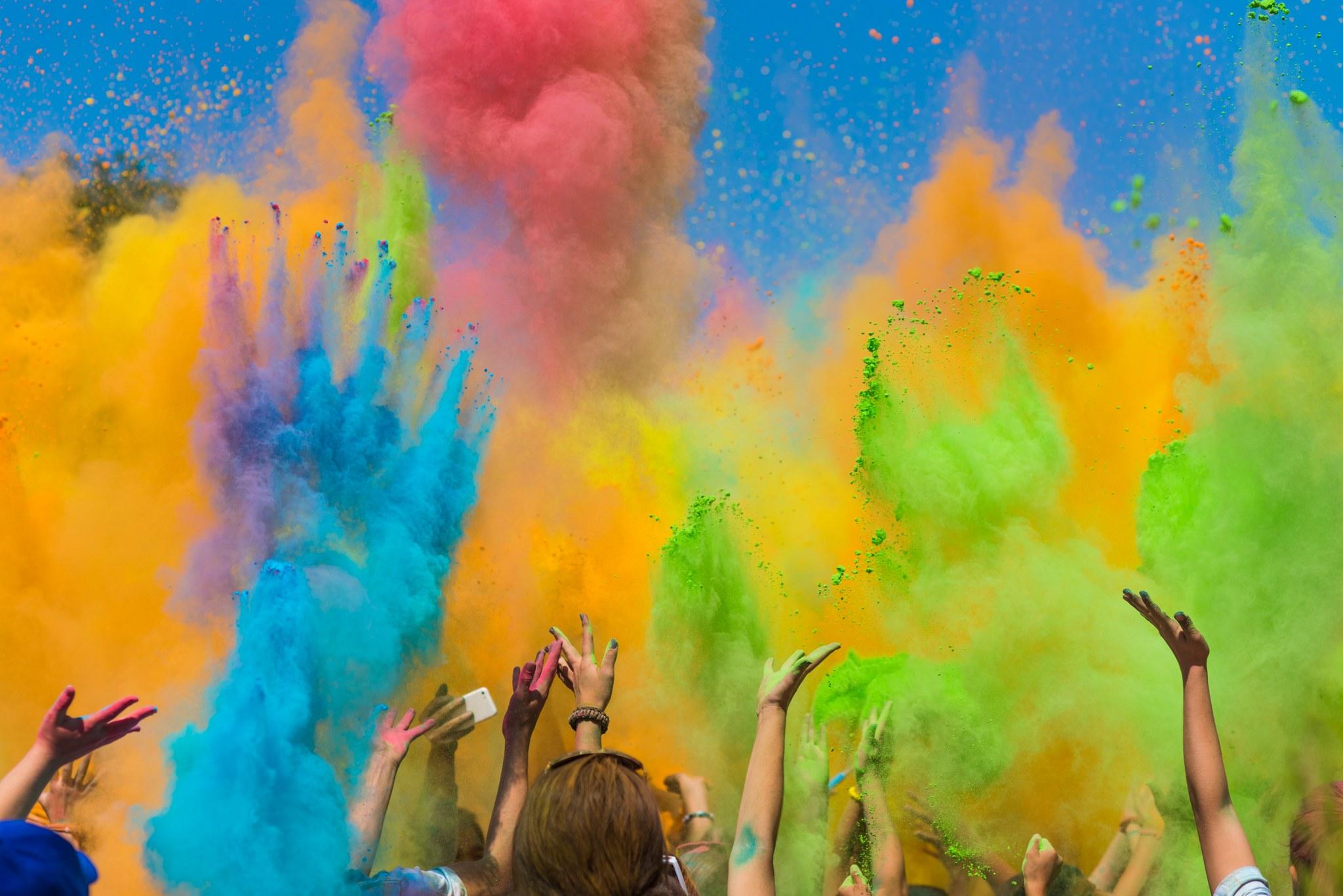 Ihmiset heittämässä väripulveria ilmaan.