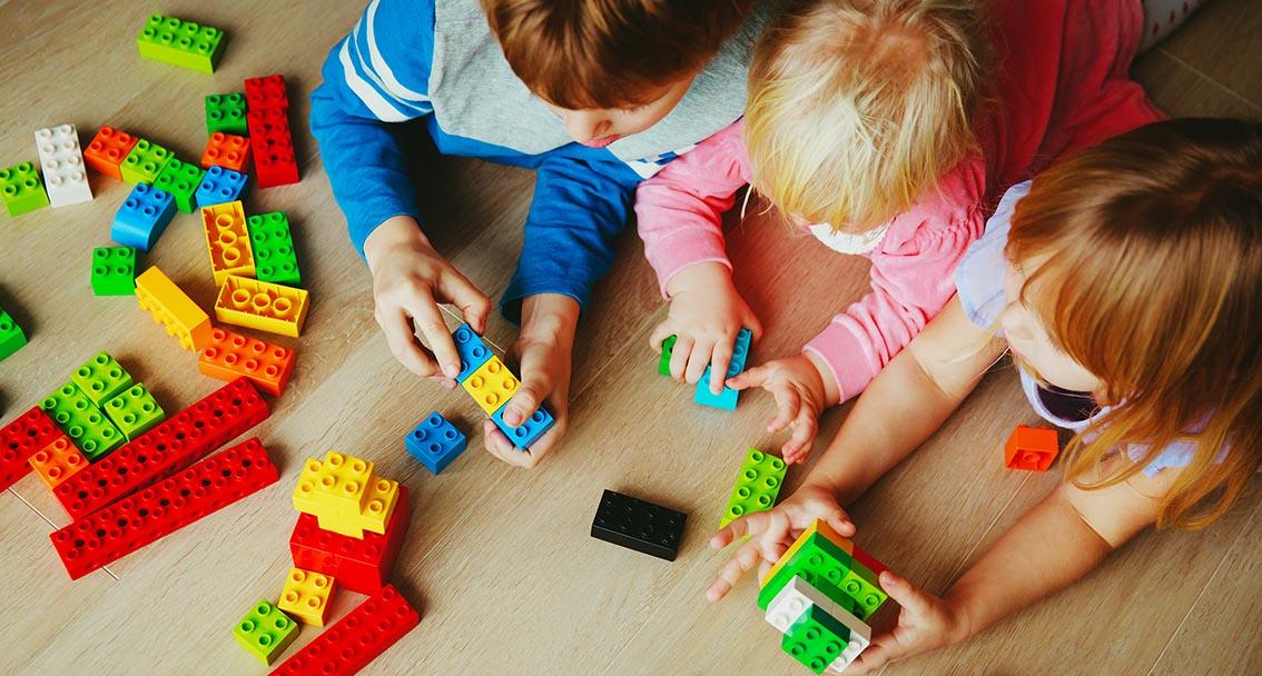 Kolme lasta leikkii yhdessä legopalikoilla.