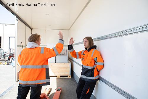 Kaksi työtakeissa olevaa opiskelijaa lyö kädet yhteen onnistumisen merkiksi.